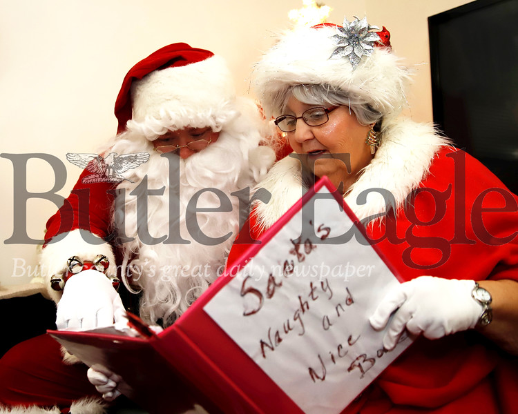 Clad in their Santa and Mrs. Claus garb, Glen Gitzen and his mother Becky read over their real life 'Naughty and Nice List.' The duo recieve real wish lists of kids prior to some of their events. Seb Foltz/Butler Eagle