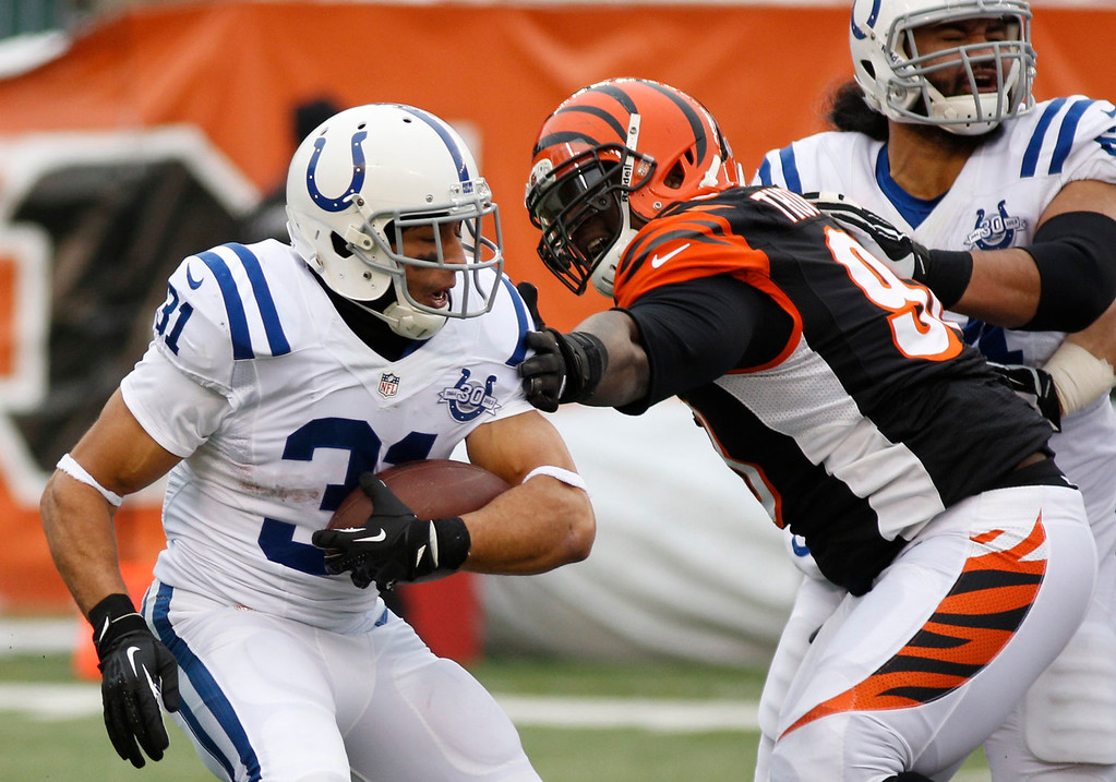 . Indianapolis Colts running back Donald Brown (31) is pursued by Cincinnati Bengals defensive tackle Brandon Thompson in the first half of an NFL football game, Sunday, Dec. 8, 2013, in Cincinnati. (AP Photo/David Kohl)