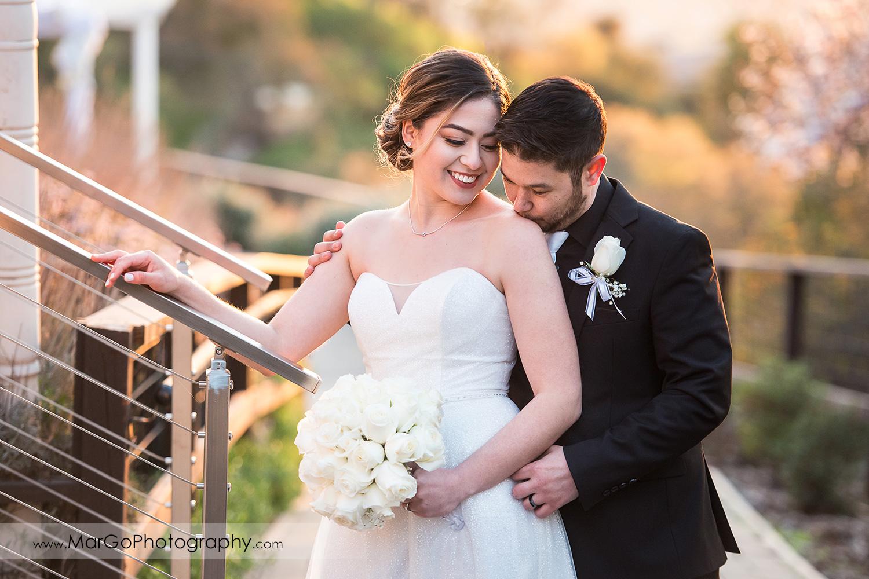 groom kissing bride's arm at Mt Hamilton GrandView Restaurant in San Jose