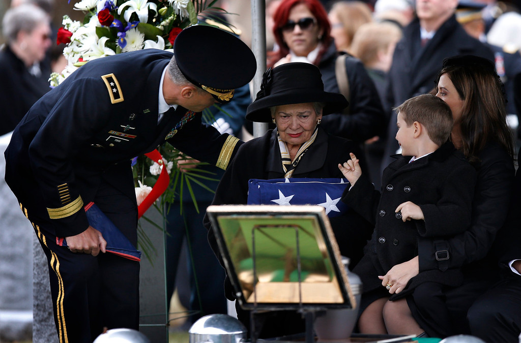 . Brenda Schwarzkopf, widow of the late U.S. Four Star General H. Norman Schwarzkopf, is comforted by U.S. Army Major. General. Kenneth Tovo (L) and her grandson Max and daughter Cindy (R) at her late husband\'s graveside while holding an American flag at Schwarzkopf\'s burial service at the United States Military Academy at West Point, New York, February 28, 2013. REUTERS/Mike Segar