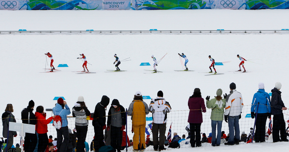 . The pack passes by spectators during the Cross Country portion of the Nordic Combined Individual normal hill event at the Vancouver 2010 Olympics in Whistler, British Columbia, Canada, Sunday, Feb. 14, 2010. (AP Photo/Matthias Schrader)