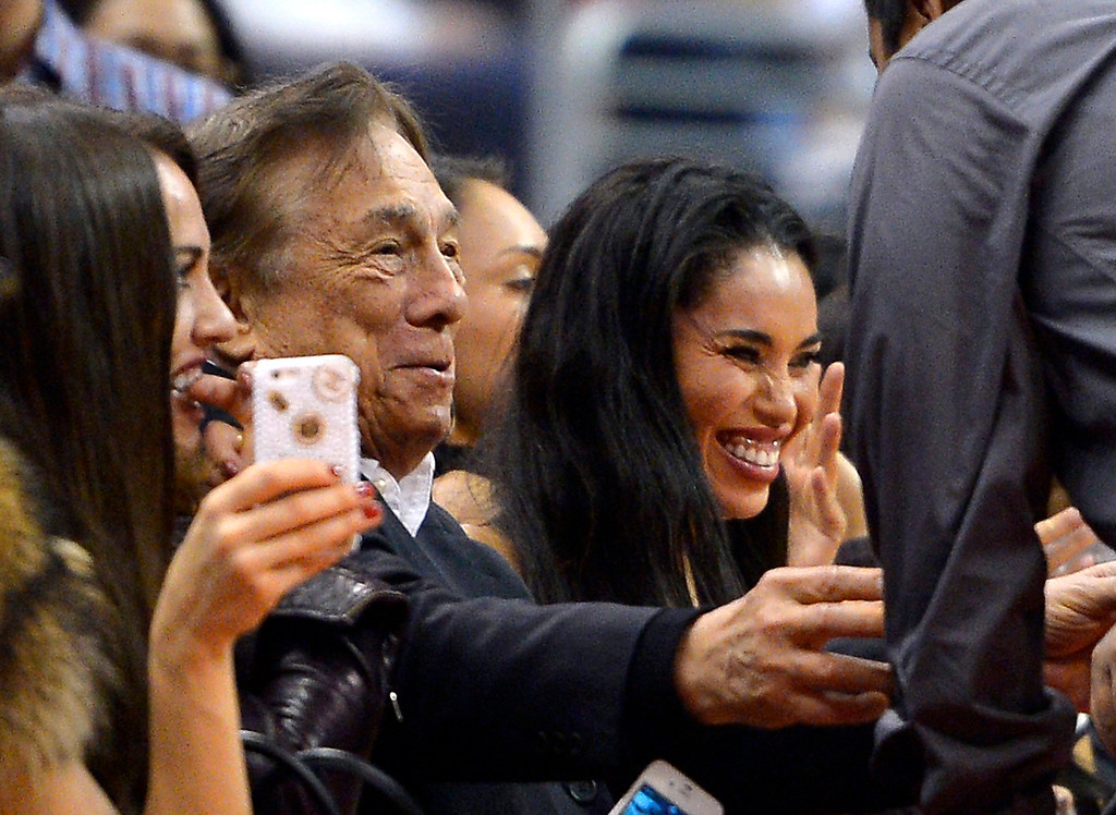 ". In this photo taken on Friday, Oct. 25, 2013, Los Angeles Clippers owner Donald Sterling, center, and V. Stiviano, right, watch the Clippers play the Sacramento Kings during the first half of an NBA basketball game, in Los Angeles. The NBA is investigating a report of an audio recording in which a man purported to be Sterling makes racist remarks while speaking to his Stiviano.  NBA spokesman Mike Bass said in a statement Saturday, April 26, 2014, that the league is in the process of authenticating the validity of the recording posted on TMZ\'s website. Bass called the comments ""disturbing and offensive.\""  (AP Photo/Mark J. Terrill)"