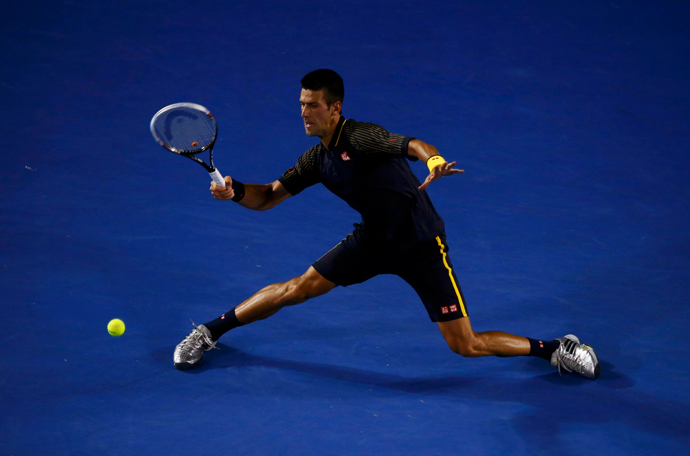 . Novak Djokovic of Serbia hits a return to David Ferrer of Spain during their men\'s singles semi-final match at the Australian Open tennis tournament in Melbourne, January 24, 2013. REUTERS/David Gray