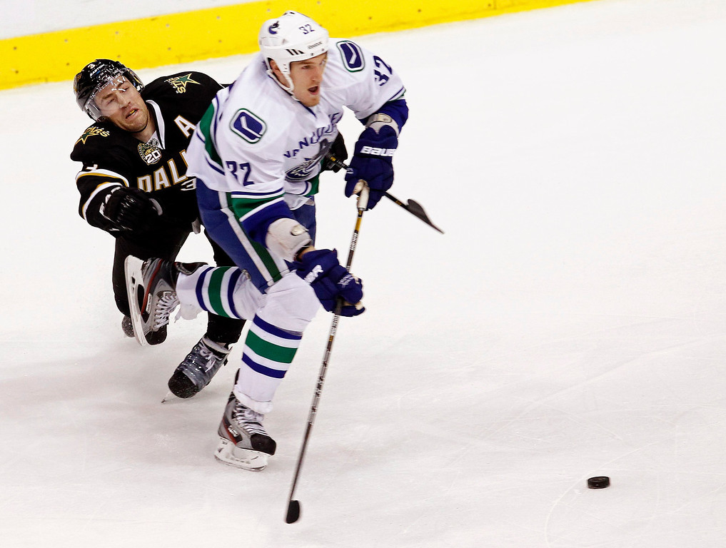 . Vancouver Canucks Dale Weise (32) skates the puck past Dallas Stars Stephane Robidas during the first period of their NHL hockey game in Dallas, Texas February 21, 2013.  REUTERS/Mike Stone