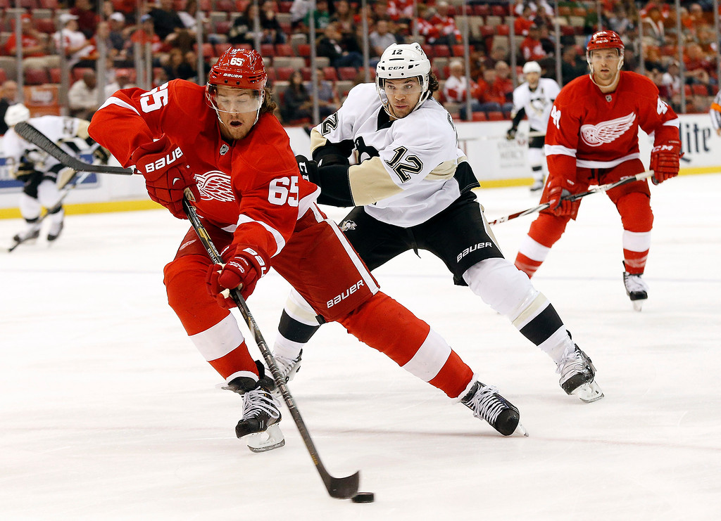 . Detroit Red Wings defenseman Danny DeKeyser (65) passes as Pittsburgh Penguins\'  Daniel Carcillo (12) defends in the first period of a NHL preseason hockey game in Detroit Wednesday, Oct. 1, 2014. (AP Photo/Paul Sancya)