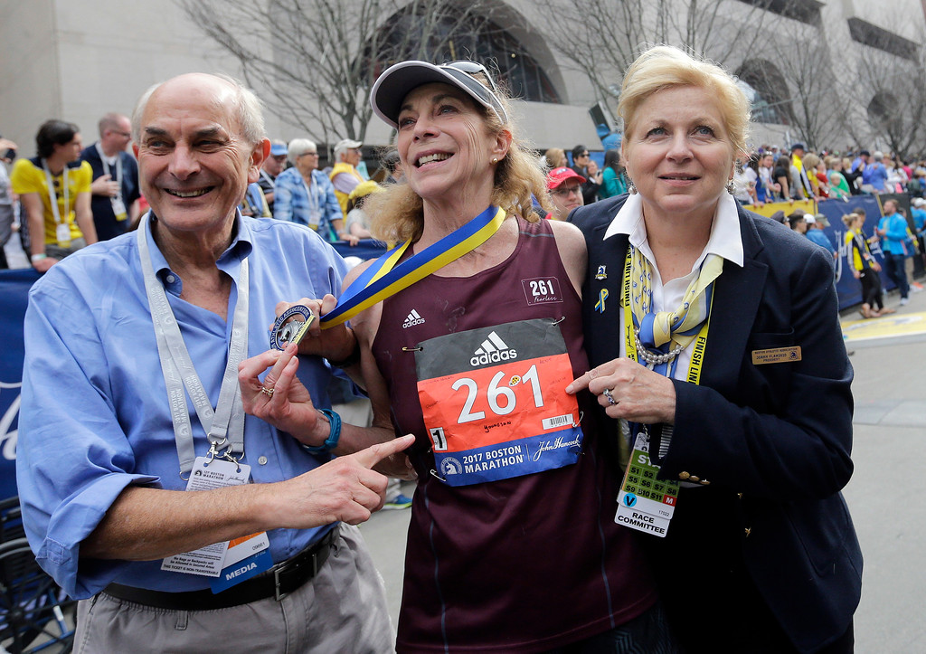 . Kathrine Switzer, center, the first official woman entrant in the Boston Marathon 50 years ago, wears the same bib number after finishing the marathon on Monday, April 17, 2017, in Boston. With Switzer are her husband Roger Robinson, left, and Joann Flaminio, right, of the Boston Athletic Association. (AP Photo/Elise Amendola)