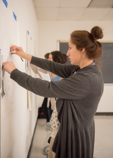 Student Amanda Galindo measures the spacing on her self-portrait in Drawing III.