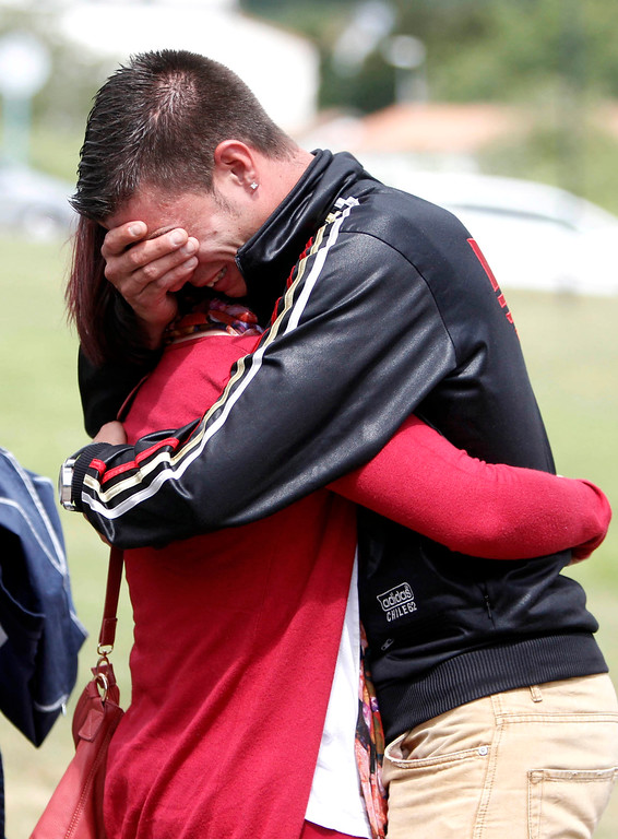 . Relatives of the victims involved in Wednesday\'s train accident react at a victims information point in Santiago de Compostela, Spain, on Thursday, July 25, 2013. Relatives of victims from a train crash in northwestern Spain sobbed and hugged each other Thursday near a makeshift morgue in a sports arena for the victims as the death toll rose to 78 and investigators tried to determine the cause. The train jumped the tracks and at least one passenger told a radio station that it appeared to be going very fast as it went into a pronounced curve while approaching the station in this Catholic shrine city on the eve of a major religious festival. (AP Photo/ Salome Montes)