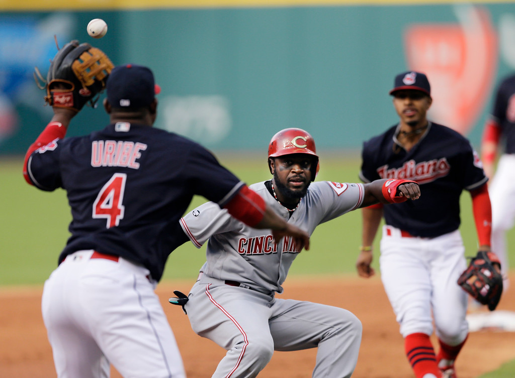 . Cincinnati Reds\' Brandon Phillips, center, is caught trying to steal third base as Cleveland Indians\' Juan Uribe, left, and Francisco Lindor defend in the first inning of an interleague baseball game, Monday, May 16, 2016, in Cleveland. Uribe tagged out Phillips on the play. (AP Photo/Tony Dejak)