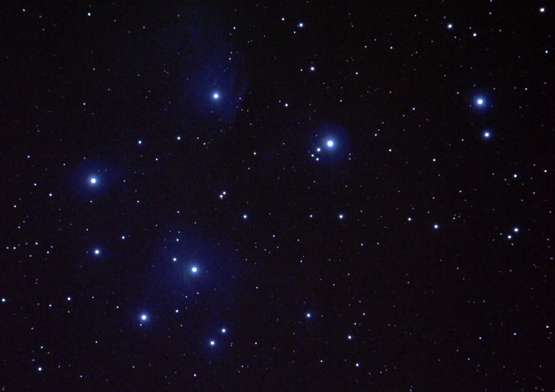 Messier M45 Pleiades, Seven Sisters, Subaru or Matariki - 31/10/2010 (Re-stacked and re-processed JPEG)  One of the most well known of open clusters, the Pleiades or Seven Sisters, located in Taurus at ~400 Light Years distance is amongst the nearest star clusters to Earth. It is the most obious cluster to the naked eye. It has been named in many ancient cultures. The cluster is dominated by hot blue and extremely luminous stars that have formed within the last 100 million years. Dust that forms a faint reflection nebulosity around the brightest stars was thought at first to be left over from the formation of the cluster, but is now known to be an unrelated dust cloud in the interstellar medium that the stars are currently passing through.  This is a reprocessing in early 2012 using Adobe Photoshop CS5 as a comparison to my original processing using GIMP, which was processed to be too blue  First 'stacked' and guided image of this extended field object. 5 images stacked using DeepSkyStacker 3.3.2 and cropped and colour adjusted by Adobe Photoshop CS5. Taken through the Apogee 80 on the SkyWatcher NEQ6 mount. Guided for 180sec @ISO 400 in-camera JPEG with no in-camera dark, no field flattener but with a light pollution filter. I took a single dark frame, but as a JPEG, and discovered afterward that darks must be RAW images, not compressed.  Things to note in this image compared to the GIMP image is that it is less blue, and that the nebulosity is less prominent as the background noise becomes too prominent if pushed any further. The black spots in the GIMP image caused by DSS hot-pixel processing have gone by not using cosmetic hot pixel detection when no dark frames are present. More light frame would be needed to gather the nebulosity, and ideally a darker sky!   Limited cropping is possible due to the size of this object so some spherical aberration is evident near the outer edges of the image. Focused using a Bahtinov Mask.   Telescope - Apogee OrthoStar LOMO 80/