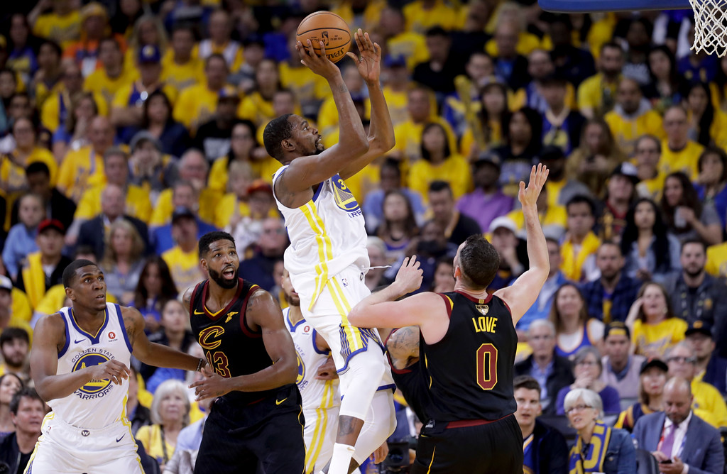 . Golden State Warriors forward Kevin Durant, top, shoots against the Cleveland Cavaliers during the second half of Game 1 of basketball\'s NBA Finals in Oakland, Calif., Thursday, May 31, 2018. (AP Photo/Marcio Jose Sanchez)