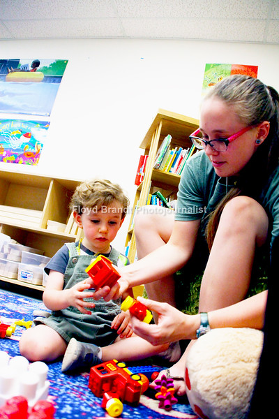 Havre Daily News/Floyd Brandt  Two year old Theodore Hill with his mother Natalie Hill having fun playing with legos at Havre Hill County Library Thursday. Lego Time and Robotics is one of many functions for children that is held at the Library.