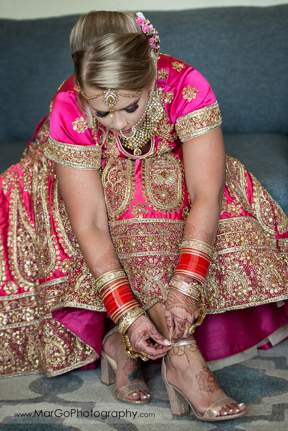 Indian bride in pink and golden dress putting on golden wedding shoes