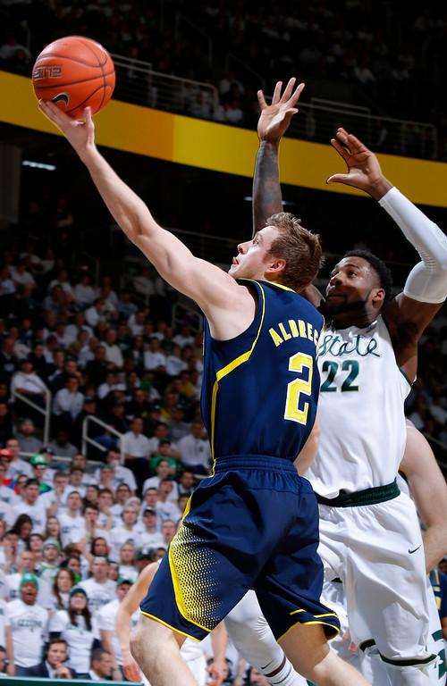 . Michigan\'s Spike Albrecht (2) puts up a layup against Michigan State\'s Branden Dawson (22) during the first half of an NCAA college basketball game, Sunday, Feb. 1, 2015, in East Lansing, Mich. (AP Photo/Al Goldis)