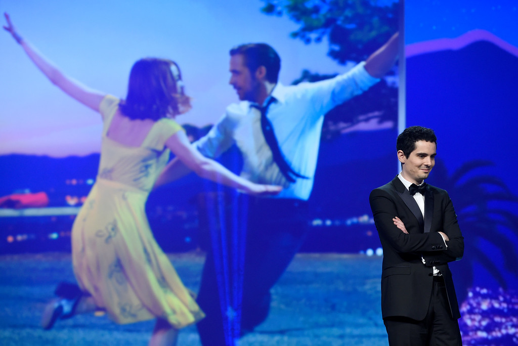 ". Damien Chazelle is seen on stage before accepting the Vanguard award for ""La La Land\"" at the 28th annual Palm Springs International Film Festival Awards Gala on Monday, Jan. 2, 2017, in Palm Springs, Calif. (Photo by Chris Pizzello/Invision/AP)"