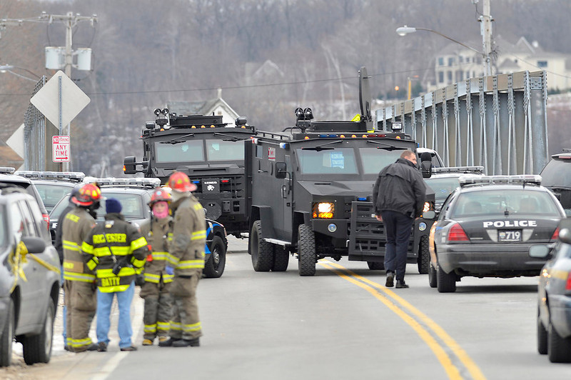 . Swat teams appear at the scene of a fire in Webster, N.Y., Monday, Dec. 24, 2012. Police in New York state say a man who killed two firefighters in a Christmas Eve ambush had served 17 years for manslaughter in the death of his grandmother. (AP Photo/Messenger Post Media, Seth Binnix)
