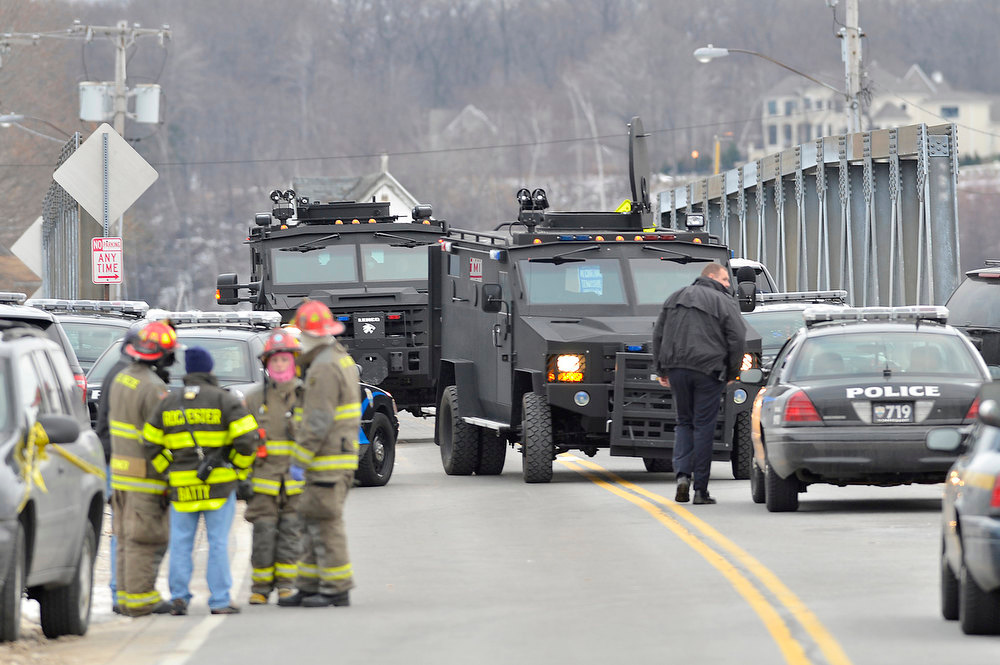 Description of . Swat teams appear at the scene of a fire in Webster, N.Y., Monday, Dec. 24, 2012. Police in New York state say a man who killed two firefighters in a Christmas Eve ambush had served 17 years for manslaughter in the death of his grandmother. (AP Photo/Messenger Post Media, Seth Binnix)