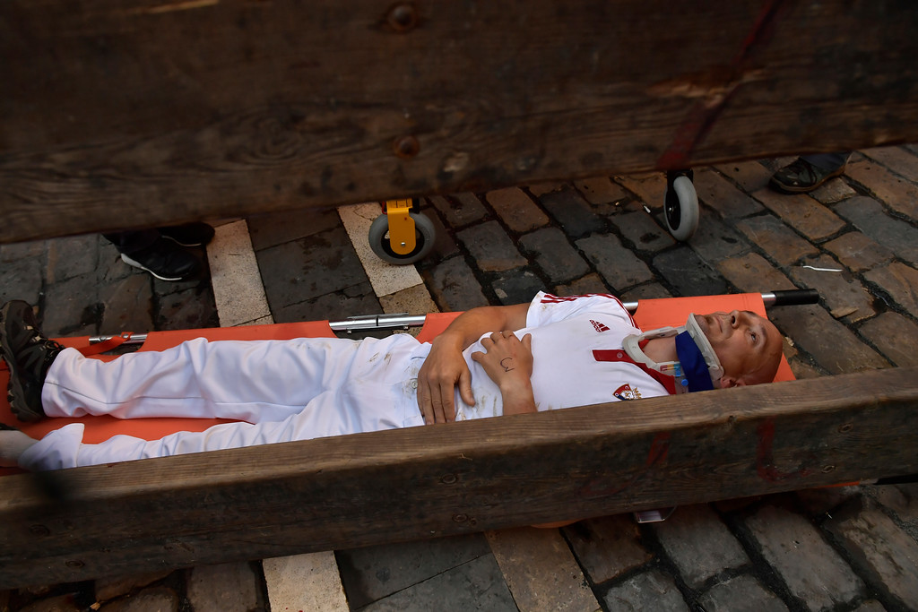 . A reveller lies on a stretcher after getting hurt during the third day of the running of the bulls at the San Fermin Festival in Pamplona, northern Spain, Monday, July 9, 2018. Revellers from around the world flock to Pamplona every year to take part in the eight days of the running of the bulls. (AP Photo/Alvaro Barrientos)