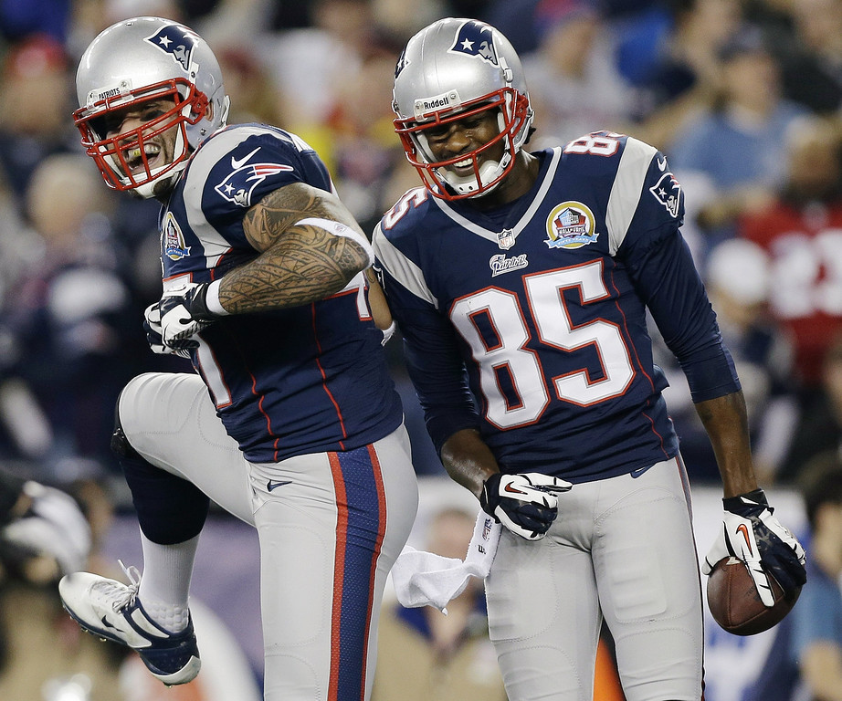 . New England Patriots wide receiver Brandon Lloyd (85) celebrates his touchdown pass with tight end Aaron Hernandez (81) during the first quarter of an NFL football game against the Houston Texans in Foxborough, Mass., Monday, Dec. 10, 2012. (AP Photo/Elise Amendola)