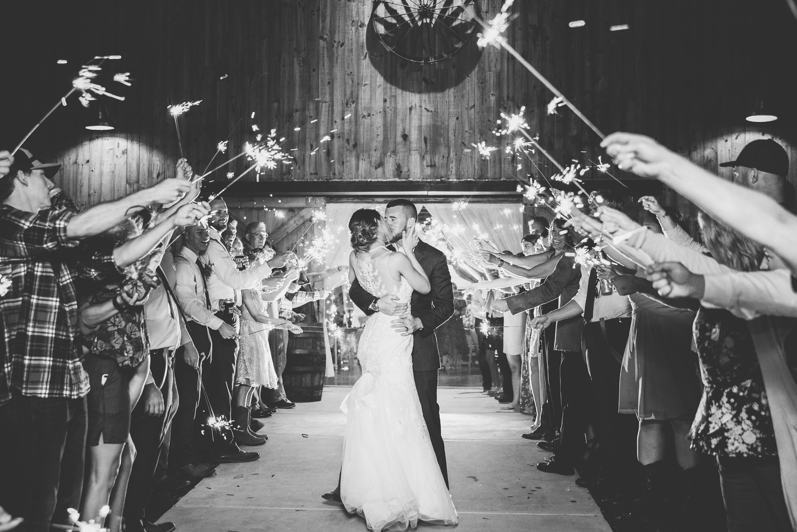 a newlywed couple kissing as they are surrounded by wedding guests holding sparklers as the make their grand exit