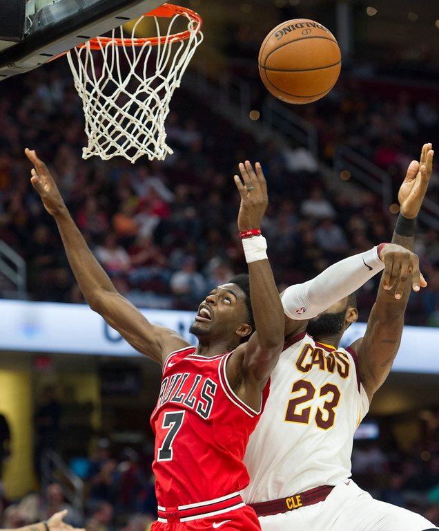 . Chicago Bulls\' Justin Holiday (7) and Cleveland Cavaliers\' LeBron James (23) go for a rebound during the second half of an NBA preseason basketball game in Cleveland, Tuesday, Oct. 10, 2017. The Bulls won 108-94. (AP Photo/Phil Long)