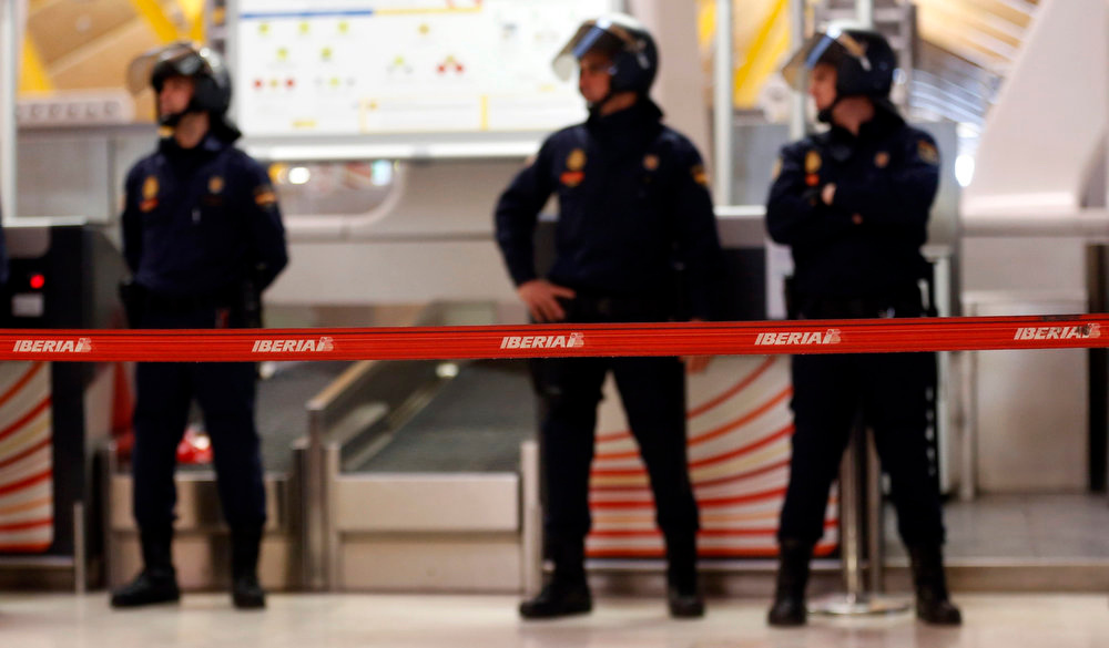 . Spanish riot police officers stand at Iberia\'s check-in area at Terminal 4 of Madrid\'s Barajas airport February 18, 2013. Striking union workers clashed with police at Madrid\'s Barajas airport on Monday on the first day of a week-long strike over more than 3,800 pending job cuts at Spain\'s flagship airline Iberia. REUTERS/Sergio Perez
