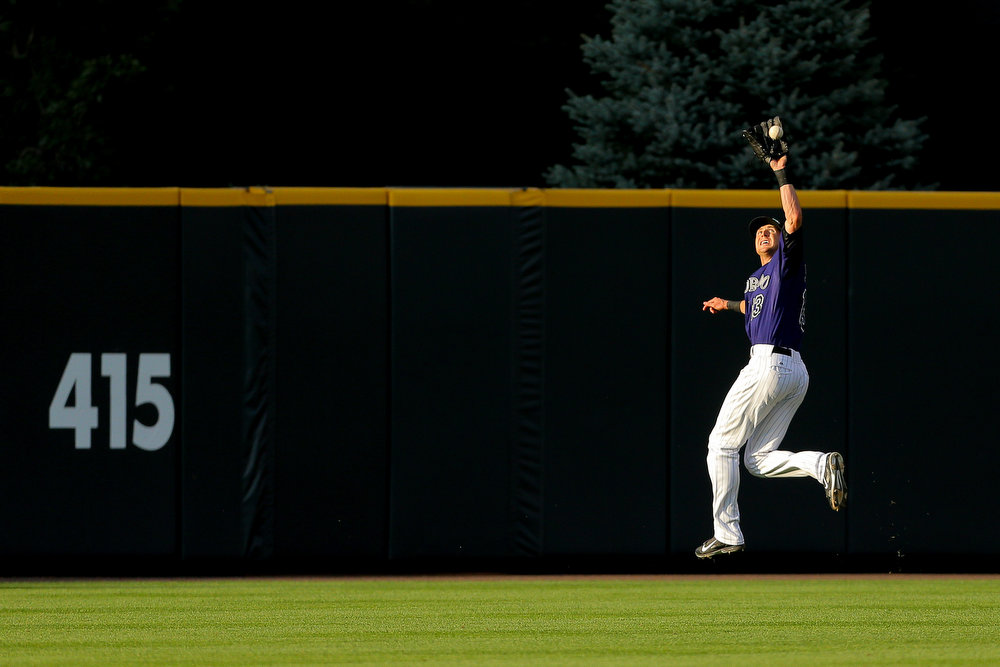 . Center fielder Drew Stubbs #13 of the Colorado Rockies makes a leaping catch for the second out of the eighth inning on a ball off the bat of Hunter Pence (not pictured) of the San Francisco Giants at Coors Field on September 1, 2014 in Denver, Colorado. The Rockies defeated the Giants 10-9 on a walk-off single by Charlie Blackmon. (Photo by Justin Edmonds/Getty Images)