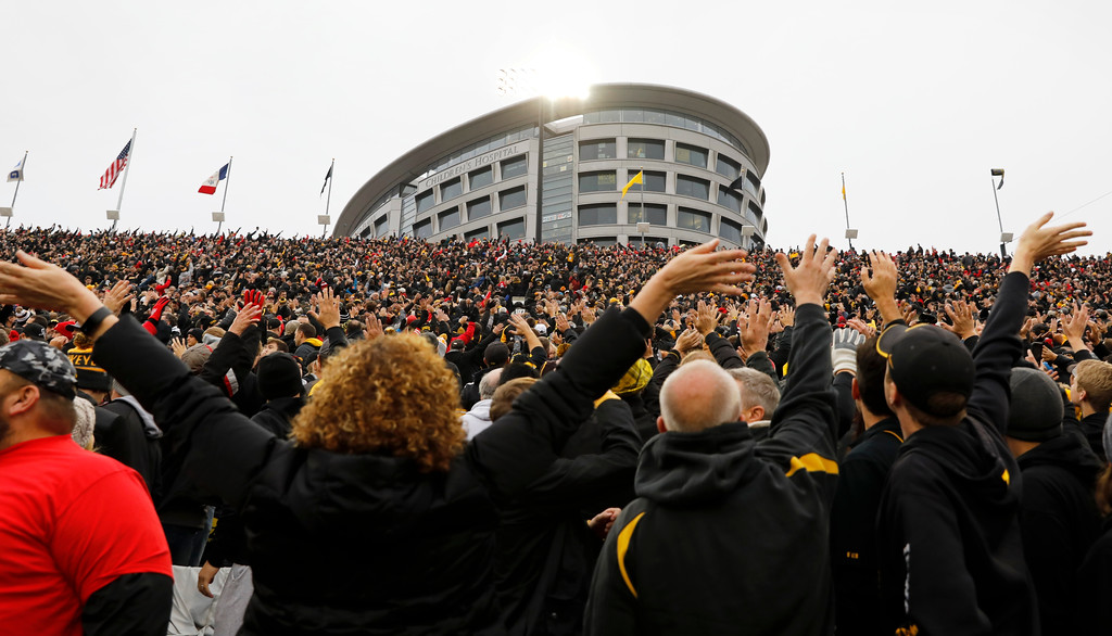 . In this Nov. 4, 2017, photo, Iowa fans wave to children in the University of Iowa\'s children\'s hospital at the end of the first quarter of an NCAA college football game against Ohio State in Iowa City, Iowa. In the new tradition, known as The Wave, at the end of the first quarter fans in the 70,585-seat Kinnick Stadium turn to wave to the pediatric patients watching from the hospital, a 12-story building that overlooks the stadium from across the street. (AP Photo/Charlie Neibergall)