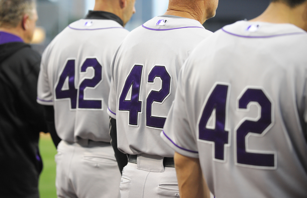 . SAN DIEGO, CA - APRIL 15: Colorado Rockies players and coaches wear #42 in honor of Jackie Robinson Day as they listen to the National Anthem before a baseball game against the San Diego Padres at Petco Park April 15, 2014 in San Diego, California.  All uniformed team members are wearing jersey number 42 in honor of Jackie Robinson Day.  (Photo by Denis Poroy/Getty Images)