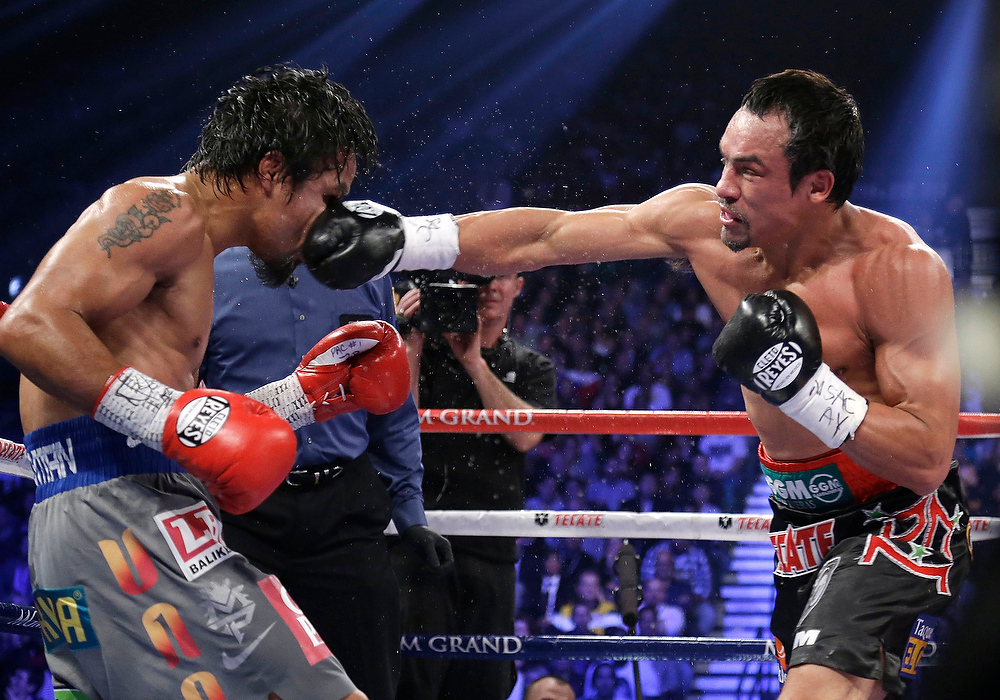 . Juan Manuel Marquez, from Mexico, right, lands a right to the head of Manny Pacquiao, from the Philippines, during their WBO world welterweight fight Saturday, Dec. 8, 2012, in Las Vegas. Marquez won by a knockout. (AP Photo/Julie Jacobson)