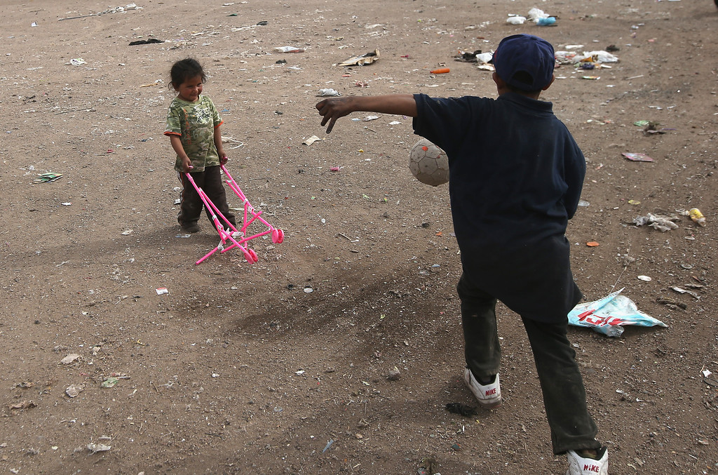 . NOGALES, MEXICO - MARCH 05:  Siblings Mirna Guadelupe, 4, and Carlos Roman, 9, play with toys found at the Tirabichi garbage dump on March 5, 2013 in Nogales, Mexico. About 30 families live at the landfill, searching for recyclables to sell for a living. Many have received protective gloves from the nearby non-profit Home of Hope and Peace, which plans to expand its assistance to Tirabichi residents.  (Photo by John Moore/Getty Images)