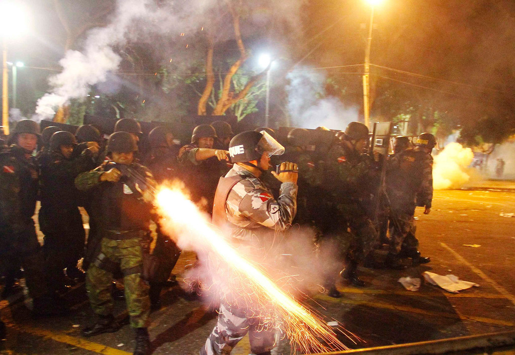. A riot policeman fires his weapon while confronting stone-throwing demonstrators during an anti-government protest in Belem, at the mouth of the Amazon River, June 20, 2013.  REUTERS/Ney Macondes