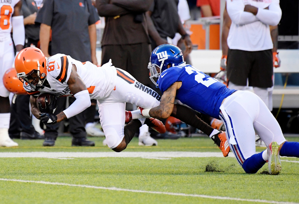 . Cleveland Browns\' Rashard Higgins (81) is tackled by New York Giants\' Darian Thompson (27) during the first half of a preseason NFL football game Thursday, Aug. 9, 2018, in East Rutherford, N.J. (AP Photo/Bill Kostroun)