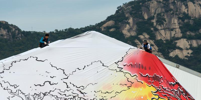 Two men fixing roof of tent, Seoul, South Korea