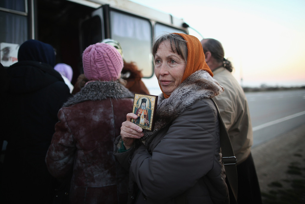 . An Orthodox clergy member carries a religious icon at a military checkpoint near a Ukrainian Air-force base on March 13, 2014 in Belbek, Ukraine. As the standoff between the Russian military and Ukrainian forces continues in Ukraine\'s Crimean peninsula, world leaders are pushing for a diplomatic solution to the escalating situation. Crimean citizens will vote in a referendum on 16 March on whether to become part of the Russian federation.  (Photo by Dan Kitwood/Getty Images)