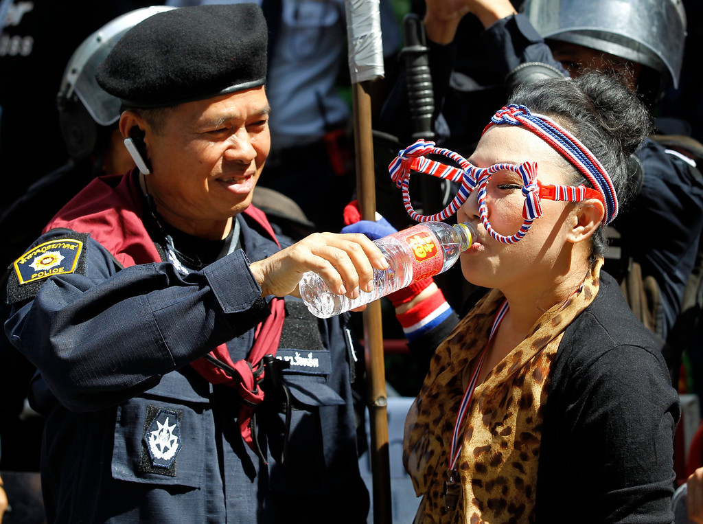 . A Thai anti-government protester (R) is given water by a policeman during a massive rally at the ruling Pheu Thai Party headquarters in Bangkok, Thailand, 29 November 2013.  EPA/RUNGROJ YONGRIT