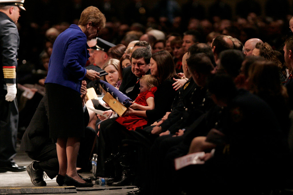 . U.S. Congreswoman Marcy Kaptur presents a flag to family members during a memorial service, Thursday, Jan. 30, 2014, at the SeaGate Convention Center in Toledo, Ohio. Toledo firefighters Stephen Machcinski, 42, and James Dickman, 31, died Sunday while fighting an apartment blaze near downtown. Firefighters found both inside the burning building, carried them out on stretchers and tried unsuccessfully to save them. Investigators have not released a cause for the fire or details about what led to their deaths. (AP Photo/J.D. Pooley)