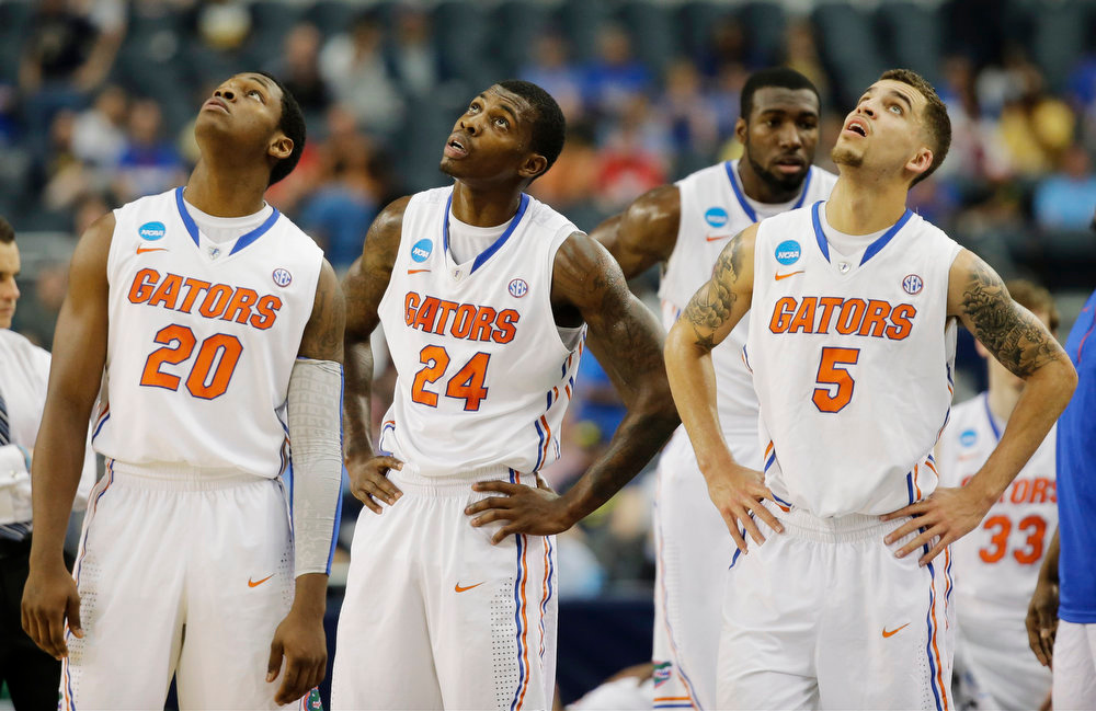Description of . Florida players Michael Frazier II (20), Casey Prather (24) and Scottie Wilbekin (5) watch the big screen during the first half of a regional final game against Michigan  in the NCAA college basketball tournament, Sunday, March 31, 2013, in Arlington, Texas. (AP Photo/David J. Phillip)