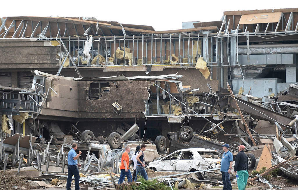 . People survey the destructions at the Moore hospital after it was hit by a tornado that destroyed buildings and overturned cars in Moore, Oklahoma, May 20, 2013.  A huge tornado with winds of up to 200 miles per hour (320 kph) devastated the Oklahoma City suburb of Moore on Monday, ripping up at least two elementary schools and a hospital and leaving a wake of tangled wreckage. REUTERS/Gene Blevins