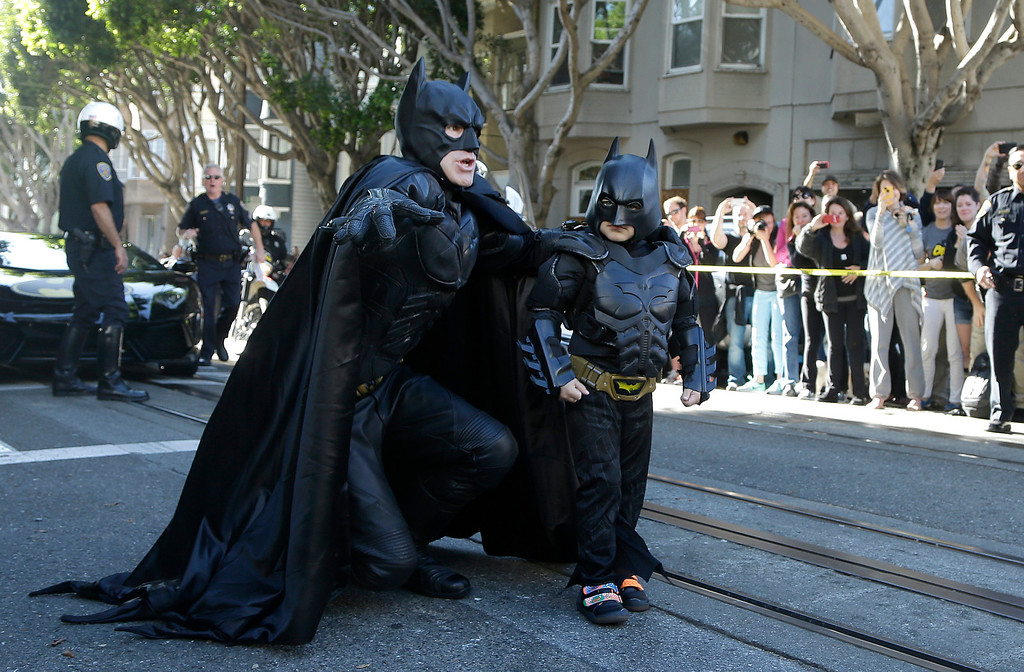 ". Miles Scott, dressed as Batkid, right, walks with Batman before saving a damsel in distress in San Francisco, Friday, Nov. 15, 2013.  San Francisco turned into Gotham City on Friday, as city officials helped fulfill Scott\'s wish to be ""Batkid.\"" Scott, a leukemia patient from Tulelake in far Northern California, was called into service on Friday morning by San Francisco Police Chief Greg Suhr to help fight crime, The Greater Bay Area Make-A-Wish Foundation says. (AP Photo/Jeff Chiu)"