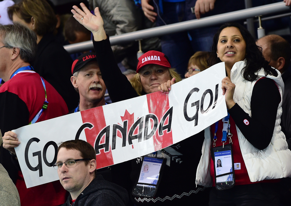. Canadian fans cheer for their team during the Men\'s Curling Gold Medal Game between Canada and Great Britain at the Ice Cube Curling Center in Sochi during the Sochi Winter Olympics on February 21, 2014.  JOHN MACDOUGALL/AFP/Getty Images