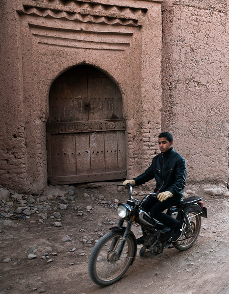 A man riding his bike past a Ksar in the skoura palmeraie.  Skoura, Morocco, 2018