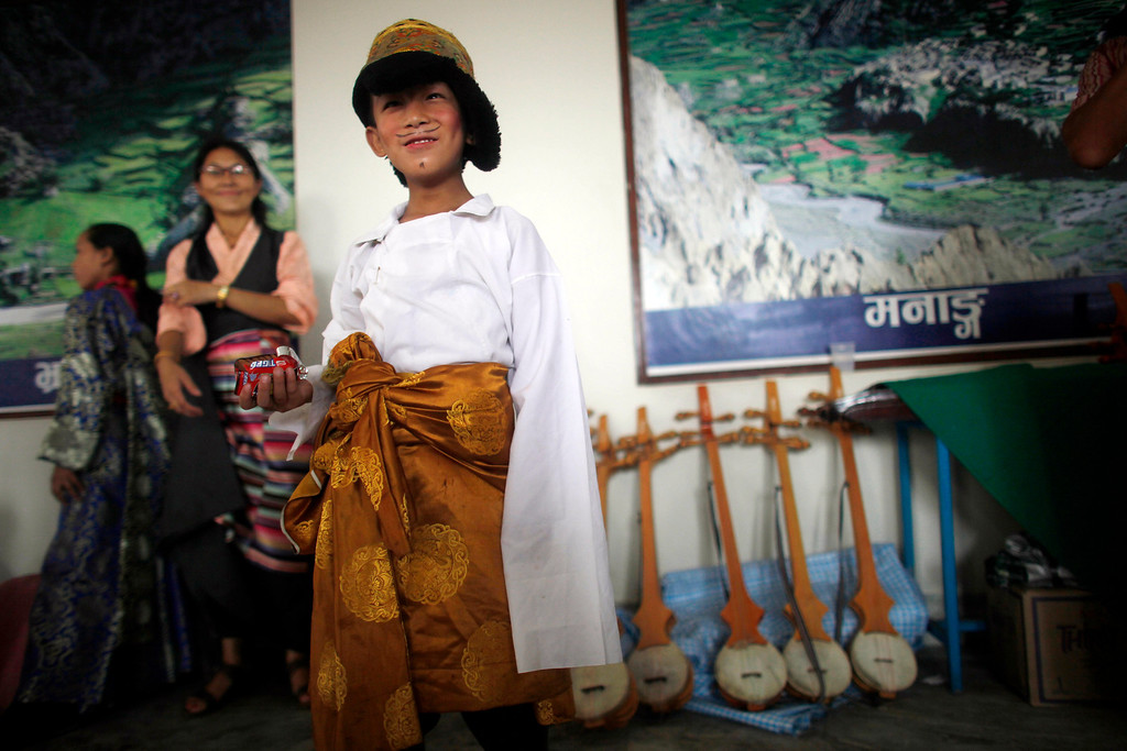 ". A young Tibetan waits to perform during celebrations to mark the birthday of their spiritual leader the Dalai Lama in Katmandu, Nepal, Saturday, July 6, 2013. Speaking after an interfaith meeting, the Dalai Lama said 150,000 Tibetans living abroad represent ""6 million Tibetans (in China) who have no freedom or opportunity to express what they feel.\"" (AP Photo/Niranjan Shrestha)"