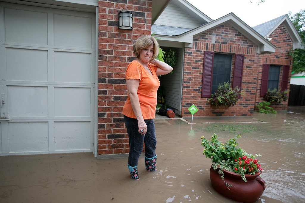 . Barbara Smitherman stands in front of her flooded home in southeast Austin, Texas, on Thursday, Oct. 31, 2013. Heavy overnight rains brought flooding to the area. The National Weather Service said more than a foot of rain fell in Central Texas, including up to 14 inches in Wimberley, since rainstorms began Wednesday.  (AP Photo/The Austin American-Statesman, Deborah Cannon)