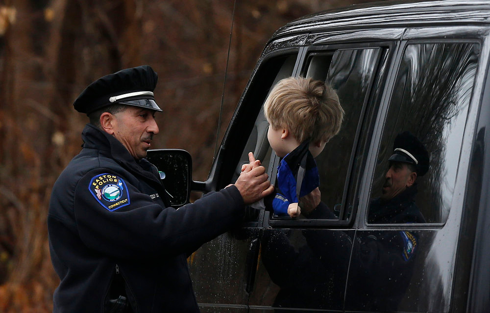 Description of . Easton police officer J. Sollazzo clasps hands with a young student returning to Hawley School, Tuesday, Dec. 18, 2012, in Newtown, Conn.  Classes resume Tuesday for Newtown schools except those at Sandy Hook. Buses ferrying students to schools were festooned with large green and white ribbons on the front grills, the colors of Sandy Hook. At Newtown High School, students in sweatshirts and jackets, many wearing headphones, betrayed mixed emotions.  Adam Lanza walked into Sandy Hook Elementary School in Newtown,  Friday and opened fire, killing 26 people, including 20 children, before killing himself.(AP Photo/Jason DeCrow)