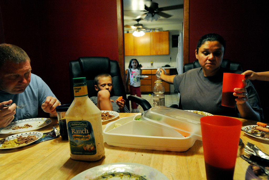 . Ena, who has an acute sense of hearing, provides for the demands of her children as the Batron family sits down for dinner at their Littleton home. She\'ll frequently call out to hear the location of the couple\'s five kids in a room.  Ena and Brent Batron are both blind, and raising their five kids under the age of 10.  Photo by Jamie Cotten, Special to The Denver Post