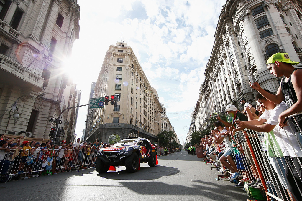 . BUENOS AIRES, ARGENTINA - JANUARY 03:  #304 Carlos Sainz and Lucas Cruz of Spain for Team Peugeot Total in the Buggy 2008 DKR Peugeot drive on the streets from the Obelisk of Buenos Aires to Plaza de Mayo podium during Day -1 of the Dakar Rally on January 3, 2015 in Buenos Aires, Argentina.  (Photo by Dean Mouhtaropoulos/Getty Images)