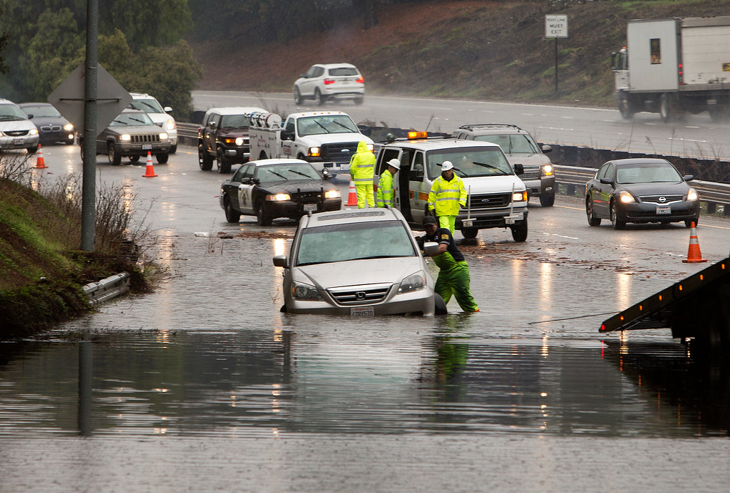 . A minivan is stuck in the flood on Highway 237 near the Dana Street exit in Mountain View, Calif., on Thursday, Dec. 11, 2014.   (LiPo Ching/Bay Area News Group)