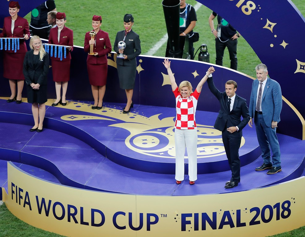 . French President Emmanuel Macron, right, and Croatian President Kolinda Grabar-Kitarovic wave at the end of the final match between France and Croatia at the 2018 soccer World Cup in the Luzhniki Stadium in Moscow, Russia, Sunday, July 15, 2018. France won 4-2. (AP Photo/Frank Augstein)