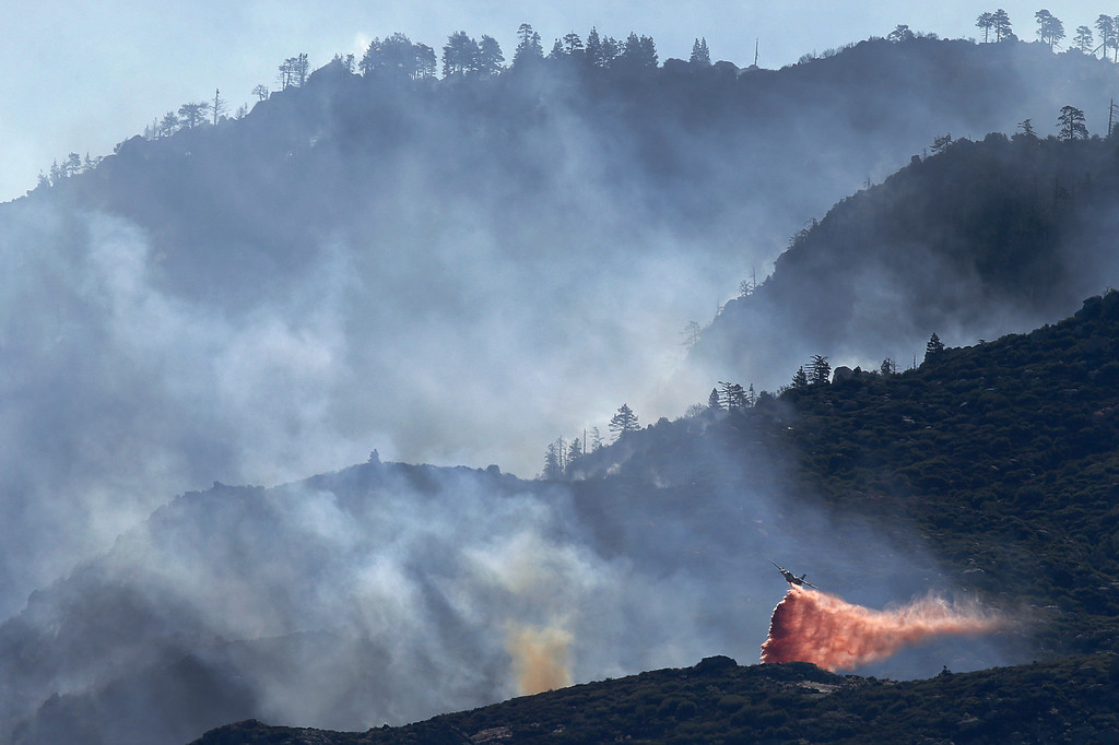. An air tanker drops fire retardant on a hot spot as firefighters continue to battle a wildfire on Friday, Aug. 9, 2013, near Banning, Calif. (AP Photo/Jae C. Hong)